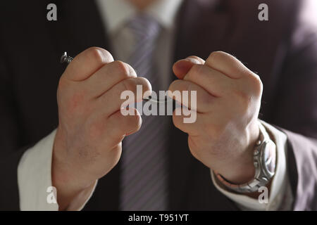 Man in suit and tie bend nail with arms closeup - Stock Photo