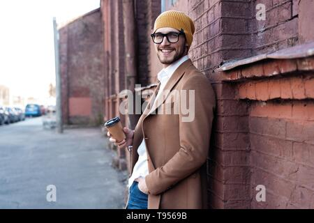 Handsome young man in casual wear holding disposable cup and smiling while walking through the city street. - Stock Photo