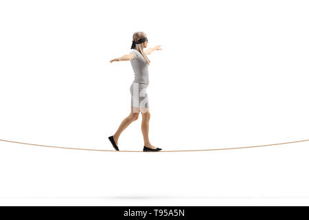 Full length profile shot of a woman walking on a rope and wearing blindfold isolated on white background - Stock Photo