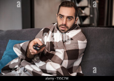 Photo of bearded man 30s having temperature and being ill while sitting wrapped in blanket on sofa at home - Stock Photo