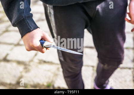 Close-up of a young man's hand with a knife, a big blade. Arrogance and violence among young people. Shallow depth of focus. - Stock Photo
