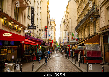 Paris, France - 24.04.2019: Latin Quarter. Narrow street of Paris among old traditional parisian houses and cafe in Paris, France - Stock Photo