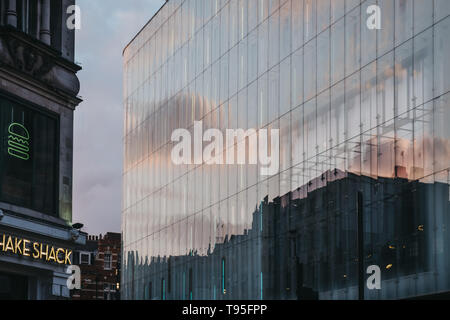 London, UK - April 14, 2019: Sky and clouds reflection on W London, luxury boutique hotel on Wardour Street, Leicester Square, London. - Stock Photo