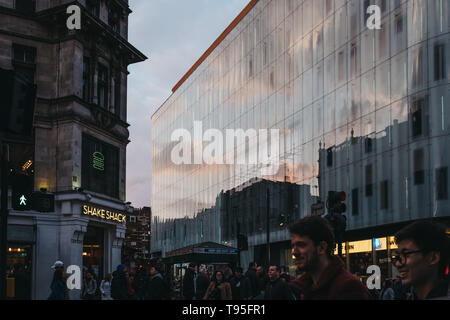 London, UK - April 14, 2019: People walking past sky and clouds reflection on W London, luxury boutique hotel on Wardour Street, Leicester Square, Lon - Stock Photo