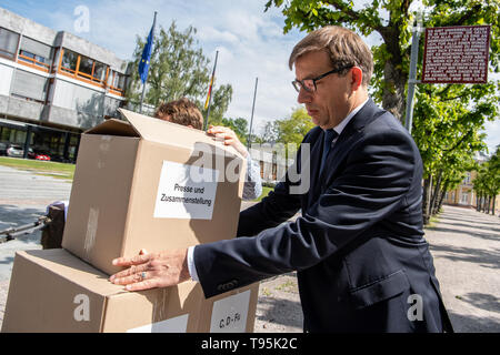 Karlsruhe, Germany. 16th May, 2019. Roman Huber, Federal Director for More Democracy, stacks a box of signature lists before the Federal Constitutional Court on the constitutional complaint against the EU's trade agreement with Singapore. The complaint by Foodwatch, Mehr Demokratie and Campact is supported by more than 13,000 citizens. Credit: Fabian Sommer/dpa/Alamy Live News - Stock Photo