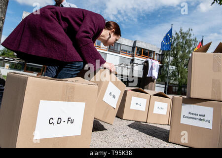 Karlsruhe, Germany. 16th May, 2019. Anne Dänner, press spokeswoman for More Democracy, has laid a box of signature lists on the constitutional complaint against the EU's trade agreement with Singapore on the floor of the Federal Constitutional Court. The complaint by Foodwatch, Mehr Demokratie and Campact is supported by more than 13,000 citizens. Credit: Fabian Sommer/dpa/Alamy Live News - Stock Photo