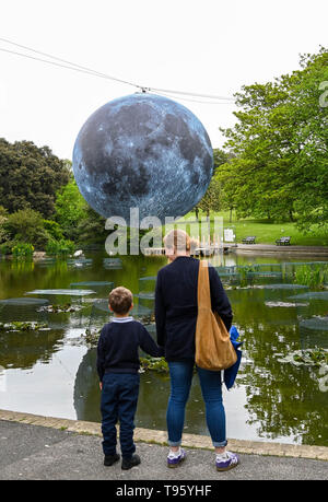 Brighton UK 30th April 2019 - A large model of the moon rises above Queens Park pond in Brighton this morning ready for tonights Brighton Festival event 'Museum of the Moon' by Luke Jerram . The moon will be lit up tonight and over the weekend accompanied by music by composer Dan Jones as it celebrates 50 years since the famous moon landing. Credit: Simon Dack / Alamy Live News - Stock Photo