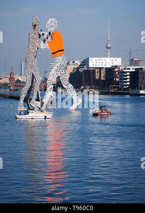 Berlin, Germany. 17th May, 2019. Activists hang from the artwork Molecule Man by US sculptor Jonathan Borofsky in the Spree River and have one of the figures put on an oversized life jacket. They protested against the European refugee policy. Credit: Annette Riedl/dpa-Zentralbild/dpa/Alamy Live News