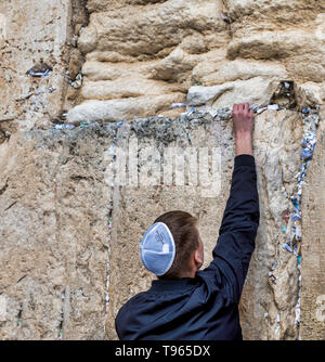 Jerusalem,israel,27-march-2019: Jewish man prays next to a crack filled with letters containing written prayers at the Western Wall in Jerusalem. Israel - Stock Photo