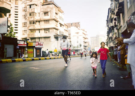 Young infant girl and her sister running alongside the runners of the  MUMBAI MARATHON 2005 - Stock Photo