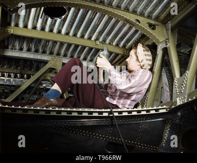 An A-20 bomber being riveted by a woman worker at the Douglas Aircraft Company plant at Long Beach, California. Although the image of 'Rosie the Riveter' reflected the industrial work of welders and riveters, the majority of working women filled non-factory positions in every sector of the economy. What unified the experiences of these women was that they proved to themselves, and the country, that they could do a man's job  and could do it well.  Photographed by Alfred T. Palmer, 1942. - Stock Photo