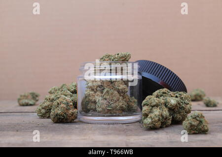 Open Glass Jar of Marijuana Sitting on Table Surrounded by Cannabis Buds - Stock Photo