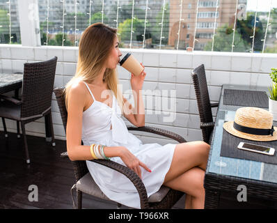 Woman in white dress, drinking coffee tea, breakfast lunch, snack restaurant, summer cafe, sitting. Dreaming thoughts, happy looking, resting after - Stock Photo