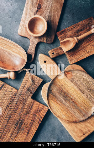 Set of wooden kitchen utensils, cutting boards, bowl, plate, mortar and pestle, scoop. Flat lay, top view - Stock Photo