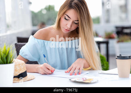 A business woman, in summer in a cafe restaurant, fills in a written contract, puts a signature on contract, making a transaction, certifying the - Stock Photo