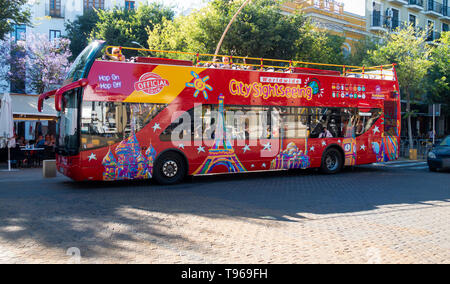 A hop on hop off City sightseeing double-decker tour bus in Seville - Stock Photo