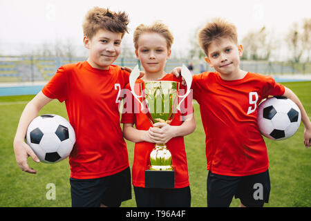 Preteen happy soccer players after final game. Boys holding golden cup and soccer balls. Sports portrait of three happy football players. Football you - Stock Photo