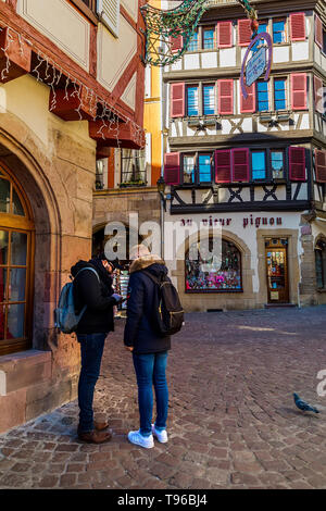 Colmar, Alsace, France, February 24, 2019.  Two man staing at cozy and beautiful streets of the French city on a sunny spring warm day - Stock Photo