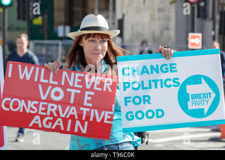 Female protester and member of the newly formed Brexit Party, demonstrates with two placards outside the House of Commons on Parliament Square, London - Stock Photo