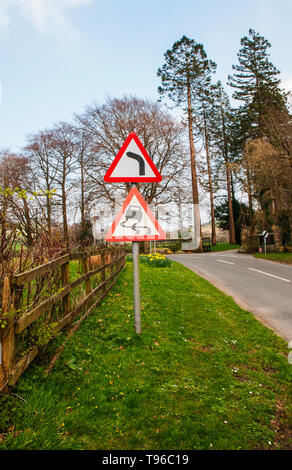 Traffic road warning signs Bend to left and Slippery road with National speed limit applies sign in distance - Stock Photo