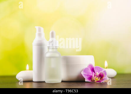 Various beauty products containers dark brown wooden table with green blurred bokeh background, copy space. - Stock Photo