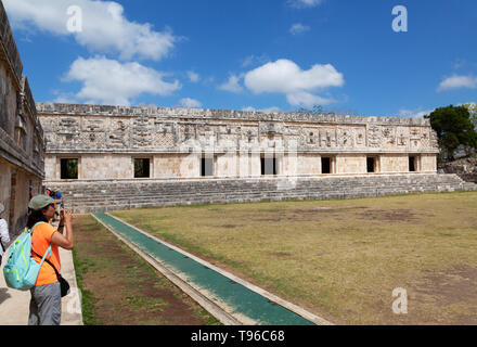 Mexico travel - a tourist taking a photo in the Nunnery Quadrangle, part of the mayan ruins at UNESCO site of Uxmal, Yucatan, Mexico Latin America - Stock Photo