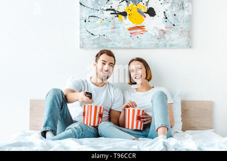 Joyful smiling couple eating popcorn in bed and watching tv - Stock Photo