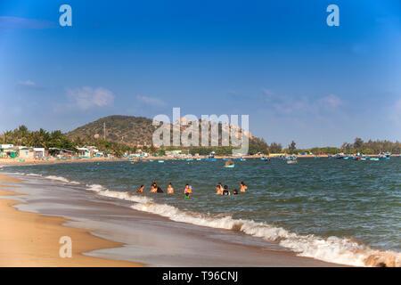 Locals people  swimming  in the sea, near Saigon Ninh Chu Resort on Phan Rang Beach,south china sea, Ninh Thuan, Vietnam - Stock Photo