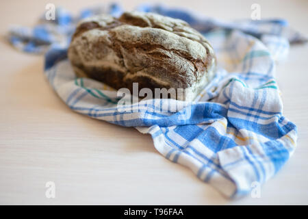 Brown bread on a table with a plaid towel - Stock Photo