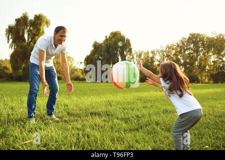 Father with a small daughter playing with a ball in nature. - Stock Photo
