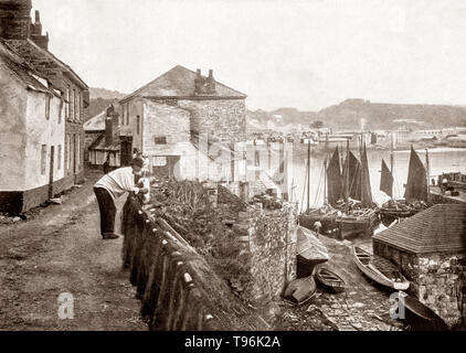A late 19th Century view of Newlyn, a seaside town and fishing port in south-west Cornwall, England. It lies on the shore of Mount's Bay and forms a small conurbation with the neighbouring town of Penzance. The principal industry was fishing, some of which can be seen in the the harbour. - Stock Photo