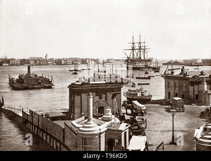 A late 19th Century view of an early small car ferry dwarfed by Admiral Nelson's flagship 'Victory' floating in the vast harbour in Portsmouth. a port city in Hampshire, England. During the 19th century,  the world's first mass production line was set up in Portsmouth Dockyard's Block Mills, making it the most industrialised site in the world and birthplace of the Industrial Revolution. Portsmouth was also the most heavily fortified town in the world, and was considered 'the world's greatest naval port' at the height of the British Empire throughout Pax Britannica. - Stock Photo