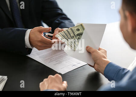 Businessman taking bribe from man. Corruption concept - Stock Photo