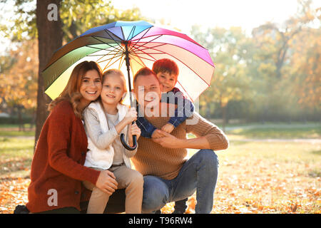 Portrait of happy family in autumn park - Stock Photo
