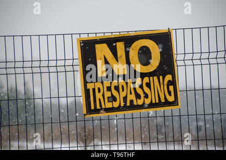 A sign that reads No Trespassing affixed to a wire fence - Stock Photo