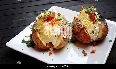 Close up of a hot baked potato topped with sour cream, green onions and cheese on black wooden board - Stock Photo