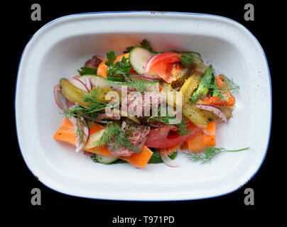 Appetizer made of roast beef and vegetables in enamel plate isolated on black balckground - Stock Photo