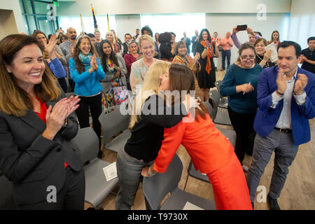 A woman politician is greeted with hugs and applause at her swearing-in for public office in Newport Beach, CA. - Stock Photo