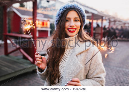 Portrait of graceful brown-haired woman in stylish white coat holding Bengal lights. Outdoor photo of romantic european girl in blue beret posing with sparklers on blur city background. - Stock Photo