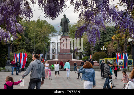 People walk during the may holidays near the monument to Vladimir Lenin, installed on the Lenin embankment in Yalta town, Republic of Crimea - Stock Photo
