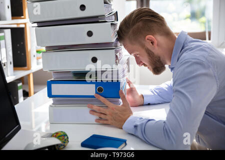 Stressed Businessman Looking At Folders While Working At Desk - Stock Photo