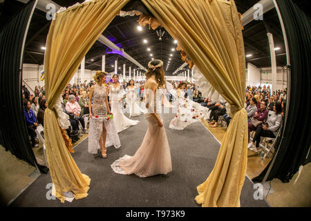 Wedding dresses are modeled by a multiracial group of women -- one wearing angel wings -- at a bridal expo in Costa Mesa, CA. - Stock Photo