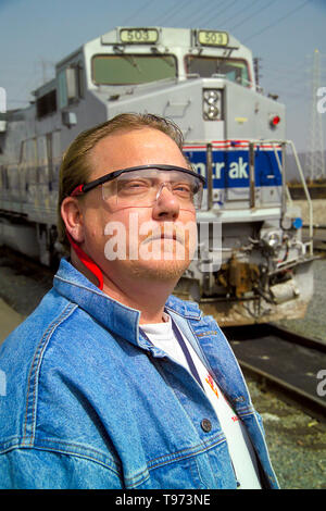 Wearing safety glasses, a train engineer poses with his locomotive in a Los Angeles railroad yard. - Stock Photo