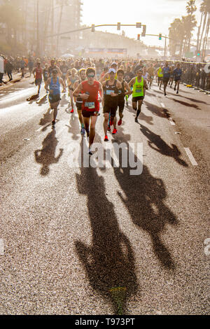 Half marathon runners throw long shadows as they leave the starting line in Huntington Beach, CA. - Stock Photo