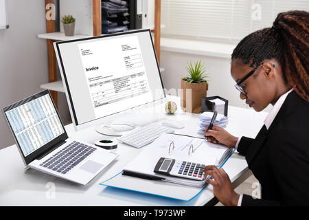 Side View Of Young Businesswoman Calculating Invoice On Computer Screen Near Laptop - Stock Photo