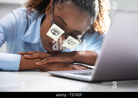 Young Woman Covering Her Eyes With Adhesive Notes On Desk In Office - Stock Photo