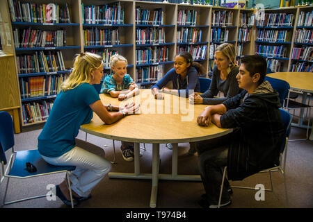 A junior high school counsellor meets with a multiethnic group of students in a San Clemente, CA, school library. - Stock Photo