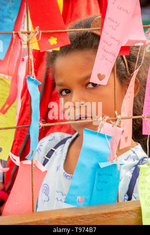 An African American 7-year-old girl reads a 'Wall of Wishes' hand-written ribbons for the Lunar New Year during a Vietnamese Tet celebration in Costa Mesa, CA. - Stock Photo
