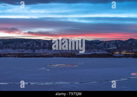 Winter Sunset at Denver Front Range - Sunset view of frozen lake and snow-covered mountains at southwest Denver, Colorado, USA. - Stock Photo