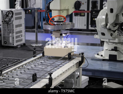 Robot arm loading carton on conveyor in manufacturing production line - Stock Photo